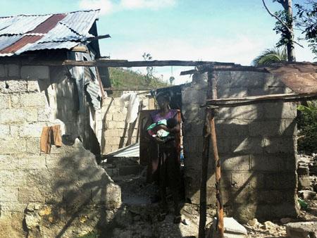 Maman et son bébé au milieu des ruines de leur maison, après le passage de l'ouragan Matthew