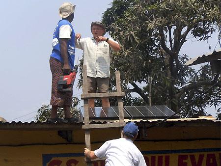 Les volontaires d'Energy Assistance installent les panneaux solaires sur le toit de l'école