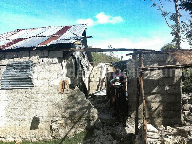 aman porte son bébé au milieu de sa maison en ruines.